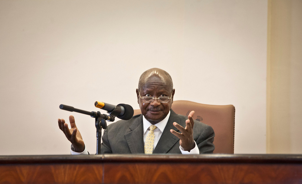 """. Uganda\'s President Yoweri Museveni gestures after signing a new anti-gay bill that sets harsh penalties for homosexual sex, in Entebbe, Uganda Monday, Feb. 24, 2014. Museveni on Monday signed the controversial anti-gay bill into law, with penalties including 14 years in jail for first-time offenders and life imprisonment as the maximum penalty for \""""aggravated homosexuality\"""", saying it is needed to deter what he called the West\'s \""""social imperialism\"""" promoting homosexuality in Africa. (AP Photo/Rebecca Vassie)"""