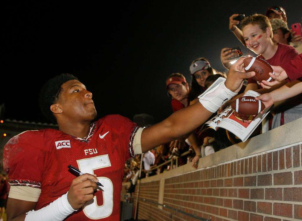 . Florida State quarterback Jameis Winston (5) signs autographs after an NCAA college football game against Idaho on Saturday, Nov. 23, 2013 in Tallahassee, Fla. Florida State beat Idaho 80-14. (AP Photo/Phil Sears)