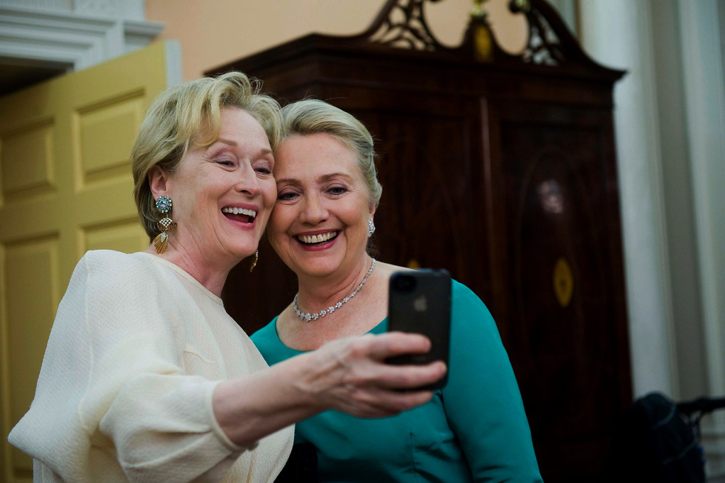 . In this Dec. 1, 2012 file photo, Actress Meryl Streep uses her iPhone to get a photo of her and Secretary of State Hillary Rodham Clinton following the State Department Dinner for the Kennedy Center Honors gala at the State Department in Washington. (AP Photo/Kevin Wolf, File)