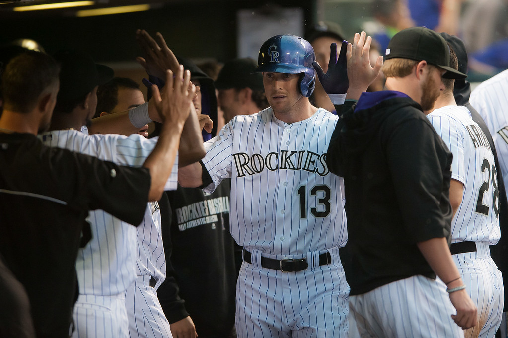 . Drew Stubbs #13 of the Colorado Rockies celebrates a fourth inning leadoff home run hit against the Pittsburgh Pirates in the dugout  at Coors Field on July 26, 2014 in Denver, Colorado.  (Photo by Dustin Bradford/Getty Images)