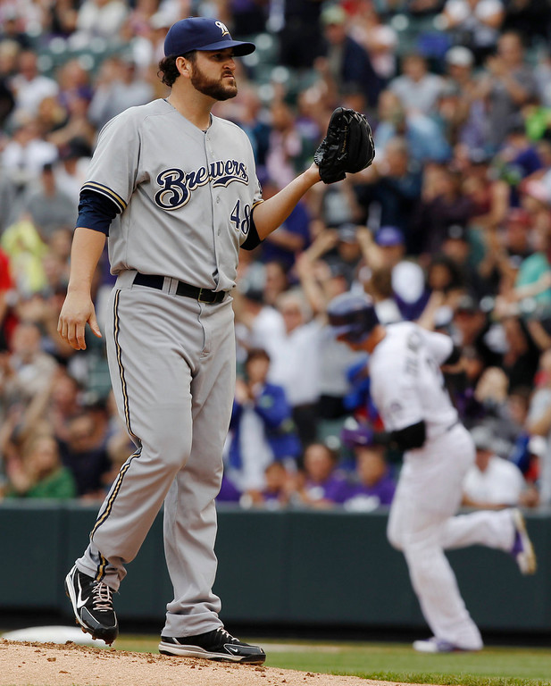 . Milwaukee Brewers starting pitcher Donovan Hand, front, calls for a new ball as Colorado Rockies\' Troy Tulowitzki, back, circles the bases after hitting a solo home run in the first inning of a baseball game in Denver on Sunday, July 28, 2013. (AP Photo/David Zalubowski)