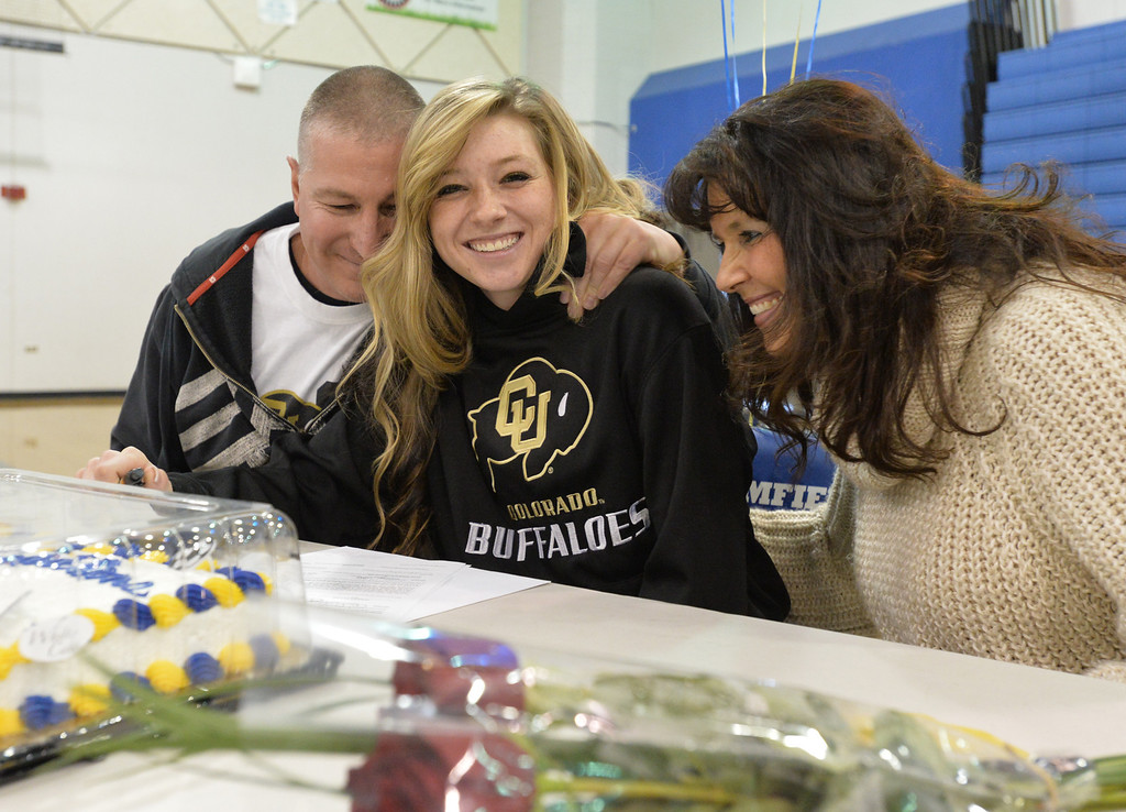 . Broomfield\'s Brittney Stark, center, is congratulated by her parents Roy and Denise after signing to the University of Colorado for soccer during National Signing Day at Broomfield High.  For more photos and video please go to broomfieldenterprise.com. February 5, 2014 staff photo/ David R. Jennings