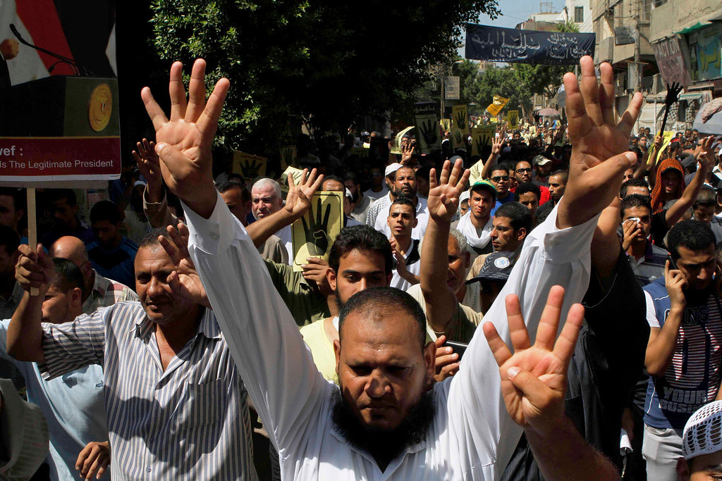 . People show a hand gesture of their open palms with four raised fingers during a protest in Beni Sueif, south of Cairo, Egypt, Friday, Aug. 30, 2013. The gesture became a symbol for the main sit-in of supporters of Egypt\'s ousted President Mohammed Morsi near the Rabaah al-Adawiya mosque in Cairo. The sit-in was violently disbanded. Several thousand people heeded calls by the Muslim Brotherhood and protested Friday throughout Cairo and other cities against a coup and deadly crackdown as the police and army blocked key roads and beefed up security. (AP Photo/Sabry Khaled, El-Shorouk)