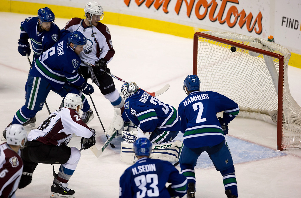 . Colorado Avalanche\'s Paul Stastny (26) scores against Vancouver Canucks goalie Jacob Markstrom, center, of Sweden, as Canucks\' Daniel Sedin (22), of Sweden; Yannick Weber (6), of Switzerland; Dan Hamhuis (2) and Henrik Sedin (33), of Sweden, and Colorado\'s Gabriel Landeskog, top, of Sweden, watch during the third period of an NHL hockey game Thursday, April 10, 2014, in Vancouver, British Columbia. (AP Photo/The Canadian Press, Darryl Dyck)