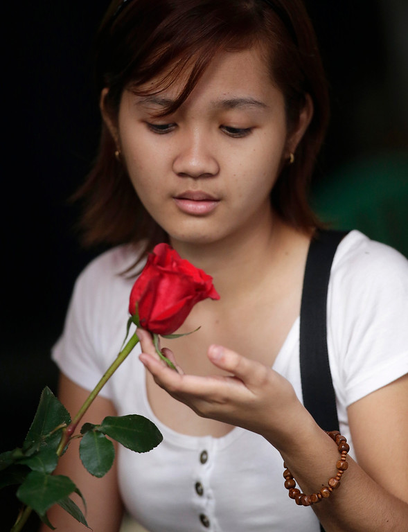 . Regina Millado holds an Ecuadorian rose she just bought that would be the centerpiece for a flower arrangement at the flower street called Dangwa on Valentine\'s Day Thursday Feb. 14, 2013 in Manila, Philippines. Business is brisk at this flower street and most of the flower shops in Manila, with red roses being the most popular among the buyers. (AP Photo/Bullit Marquez)