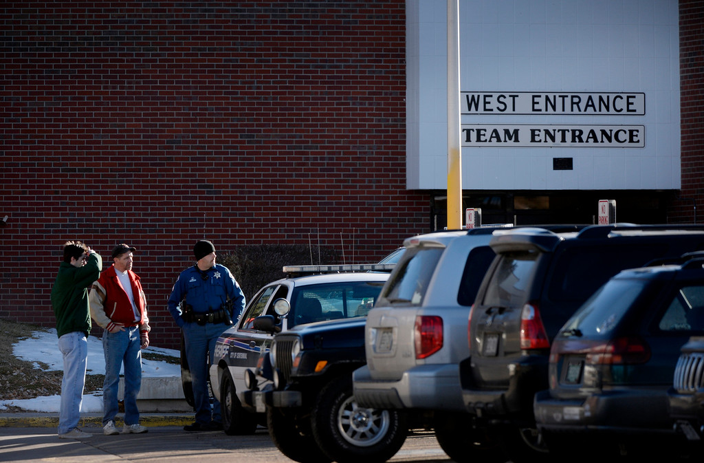 . A members of the Arapahoe County Sheriff\'s department  talks with people in a parking lot at Arapahoe High School in Centennial, CO December 14, 2013. (Photo By Craig F. Walker / The Denver Post)