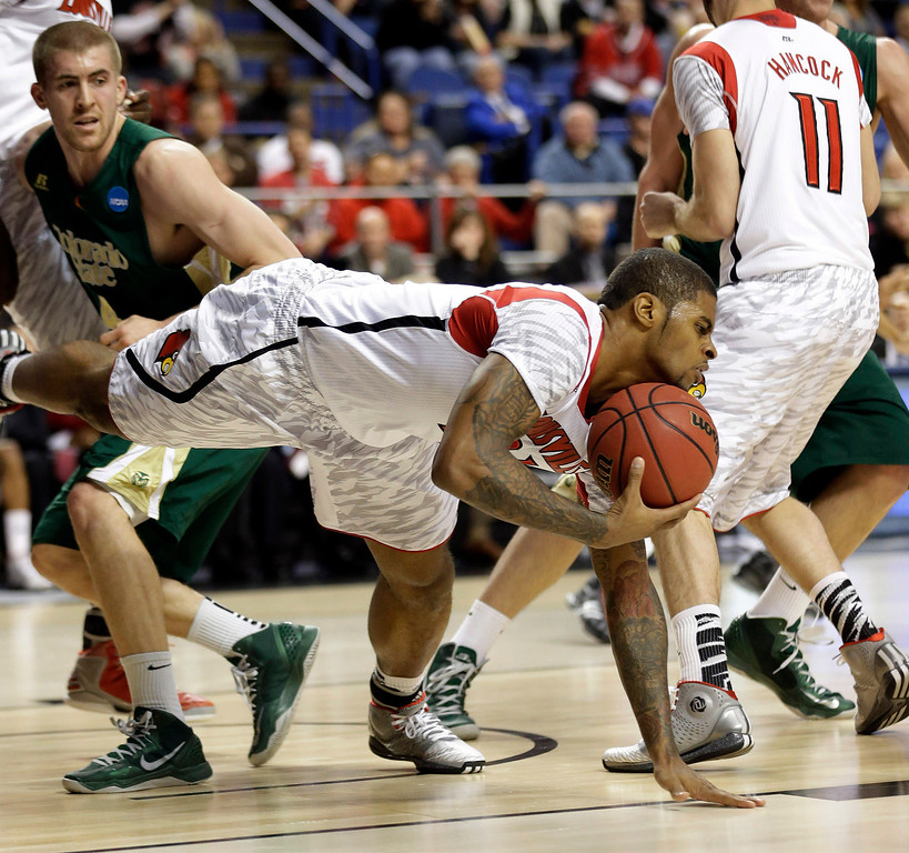 . Louisville forward Chane Behanan, center, grabs a loose ball in front of Colorado State forward Pierce Hornung (4) in the first half of a third-round NCAA college basketball tournament game on Saturday, March 23, 2013, in Lexington, Ky.  (AP Photo/John Bazemore)