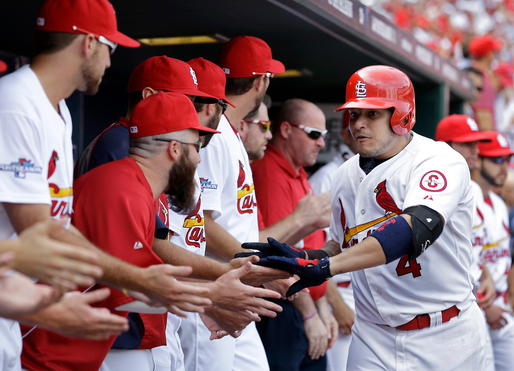 . St. Louis Cardinals\' Yadier Molina (4) is congratulated in the dugout after hitting a home run against the Pittsburgh Pirates in the fifth inning of Game 2 of baseball\'s National League division series on Friday, Oct. 4, 2013, in St. Louis. (AP Photo/Jeff Roberson)