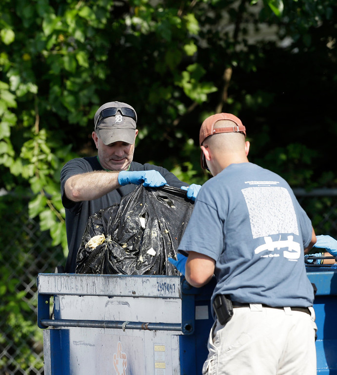 . Investigators take out a black trash bag from a dumpster Sunday, July 21, 2013 near where three bodies were recently found in East Cleveland, Ohio. Searchers rummaging through vacant houses in a neighborhood where three female bodies were found wrapped in plastic bags should be prepared to find one or two more victims, a police chief said Sunday. (AP Photo/Tony Dejak)