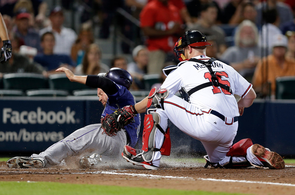 . Colorado Rockies\' Michael Cuddyer (3) is tagged out by Atlanta Braves catcher Brian McCann (16) as he tried to score on a Wilin Rosario double in the seventh inning of a baseball game in Atlanta, Tuesday, July 30, 2013. (AP Photo/John Bazemore)