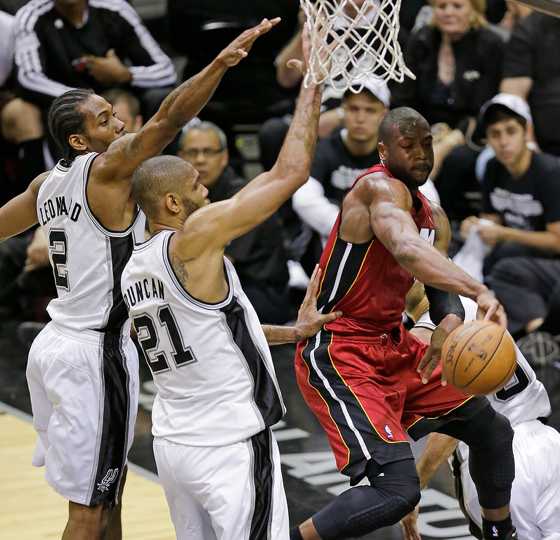 . Miami Heat\'s Dwyane Wade (3) passes around San Antonio Spurs\' Tim Duncan (21) and Kawhi Leonard (2) during the first half at Game 3 of the NBA Finals basketball series, Tuesday, June 11, 2013, in San Antonio. (AP Photo/David J. Phillip)