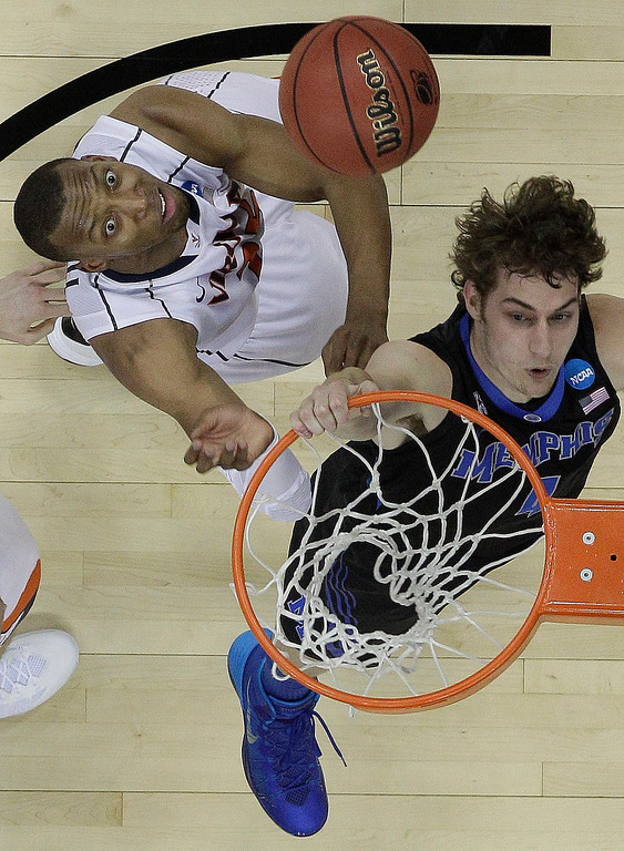. Memphis forward Austin Nichols (4) misses the basket as Virginia forward Akil Mitchell (25) looks on during the first half of an NCAA college basketball third-round tournament game, Sunday, March 23, 2014, in Raleigh. (AP Photo/Chuck Burton)