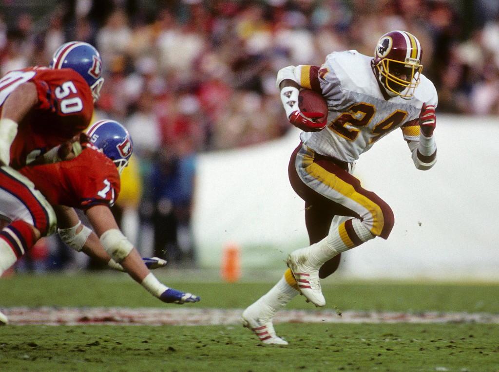 . Running back Kelvin Bryant #24 of the Washington Redskins runs with the ball under pressure from the Denver Broncos during Super Bowl XXII at Jack Murphy Stadium on January 31, 1988 in San Diego, California.  The Redskins won 42-10.  (Photo by George Rose/Getty Images)