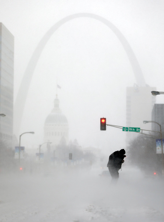 . A person struggles to cross a street in blowing and falling snow as the Gateway Arch appears in the distance Sunday, Jan. 5, 2014, in St. Louis. Snow that began in parts of Missouri Saturday night picked up intensity after dawn Sunday with several inches of snow on the ground by midmorning and more on the way. (AP Photo/Jeff Roberson)