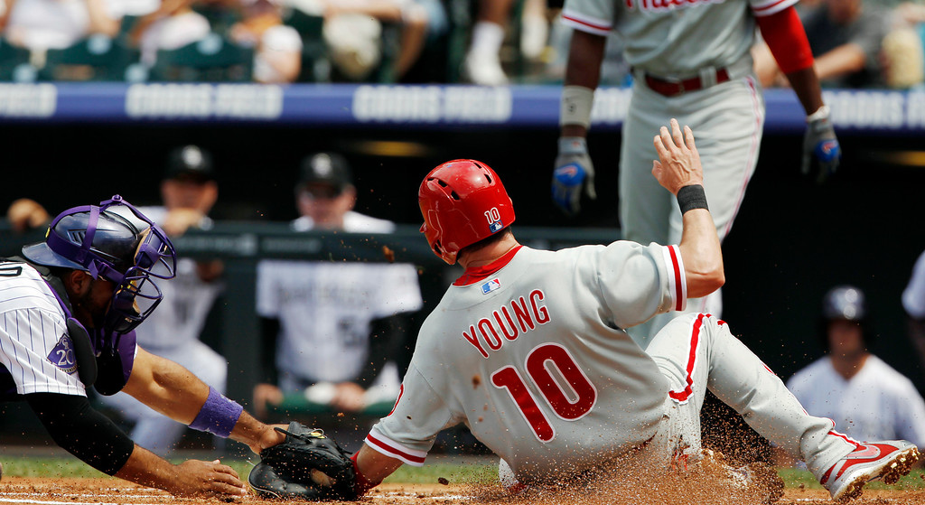 . Colorado Rockies catcher Wilin Rosario, left, tags out Philadelphia Phillies\' Michael Young at home plate in the first inning of a baseball game in Denver, Saturday, June 15, 2013. (AP Photo/David Zalubowski)