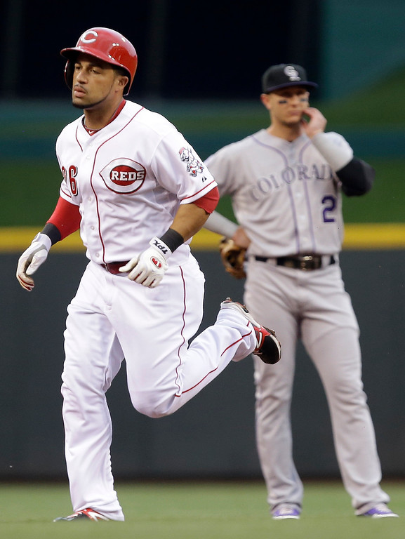 . Cincinnati Reds\' Xavier Paul rounds the bases past Colorado Rockies shortstop Troy Tulowitzki after Paul hit a three-run home run off Jon Garland in the first inning of a baseball game, Wednesday, June 5, 2013, in Cincinnati. (AP Photo/Al Behrman)
