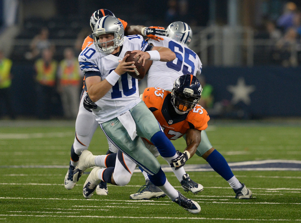 . ARLINGTON, TX - AUGUST 28: Dallas Cowboys quarterback Dustin Vaughan (10) slips a tackle by Denver Broncos linebacker Steven Johnson (53) during the second quarter August 28, 2014 at AT&T Stadium. (Photo by John Leyba/The Denver Post)