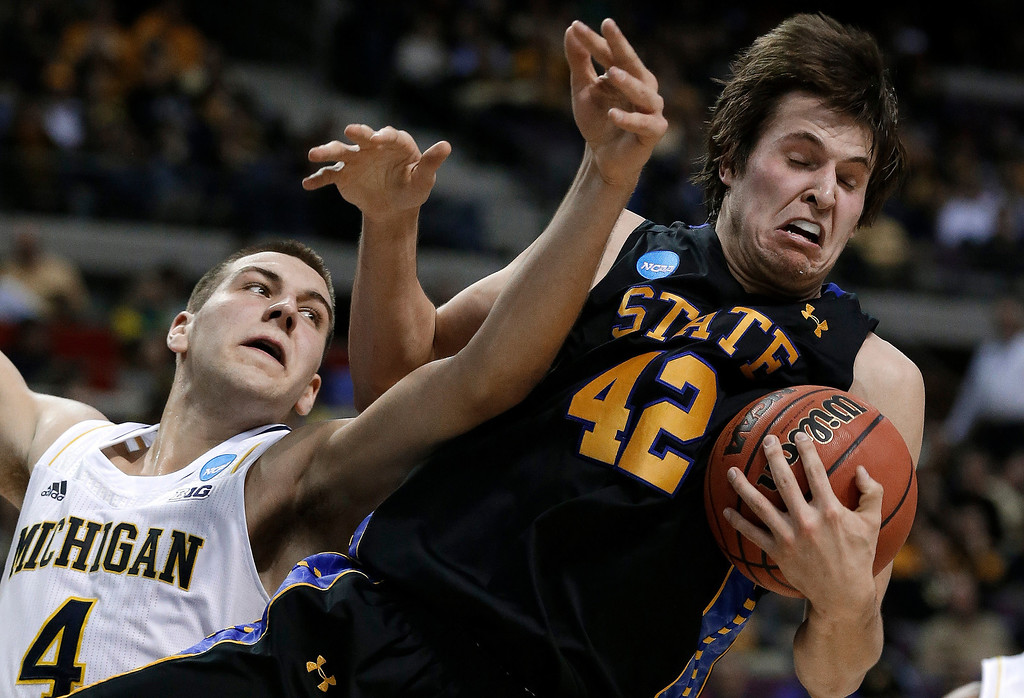 . South Dakota State forward Jordan Dykstra (42) pulls down a rebound in front of Michigan forward Mitch McGary (4) in the first half of a second-round game of the NCAA men\'s college basketball tournament in Auburn Hills, Mich., Thursday, March 21, 2013. (AP Photo/Paul Sancya)