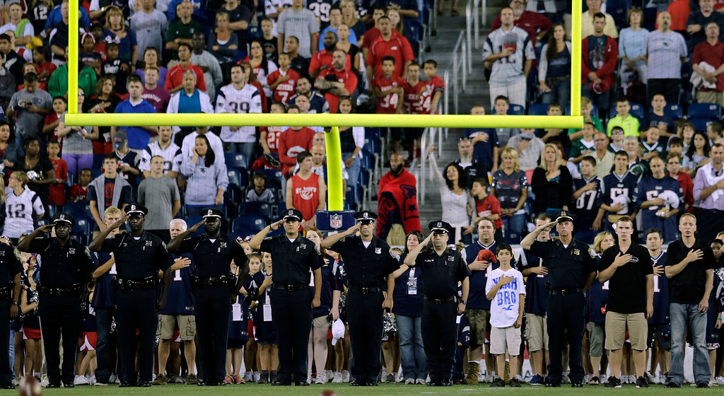 . Police from the Boston metro area join fans in tribute to  Massachusetts Institute of Technology police officer Sean Collier, killed in the aftermath of the Boston Marathon bombings, before an NFL preseason football game between the New England Patriots and the Tampa Bay Buccaneers on Friday, Aug. 16, 2013, in Foxborough, Mass. (AP Photo/Charles Krupa)