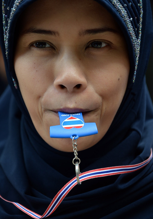 . An anti-government blows a whistle during a protest march in Bangkok on November 29, 2013. Defiant Thai opposition protesters stormed the army headquarters and besieged Prime Minister Yingluck Shinawatra\'s party offices on November 29, intensifying their fight to bring down her government.  AFP PHOTO / Indranil MUKHERJEE/AFP/Getty Images