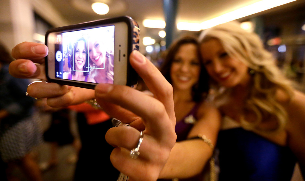 . Miss America pageant alumni Miss South Dakota Calista Kirby, left, and Miss Rhode Island Kelsey Fournier take a photograph of themselves with a phone before the Miss America 2014 pageant, Sunday, Sept. 15, 2013, in Atlantic City, N.J. The former misses participated in last year\'s contest in Las Vegas. (AP Photo/Julio Cortez)