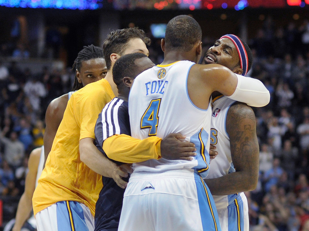 . Teammates celebrated with Ty Lawson, right, after he sunk a three-point shot late in the fourth quarter.   Photo By Karl Gehring/The Denver Post