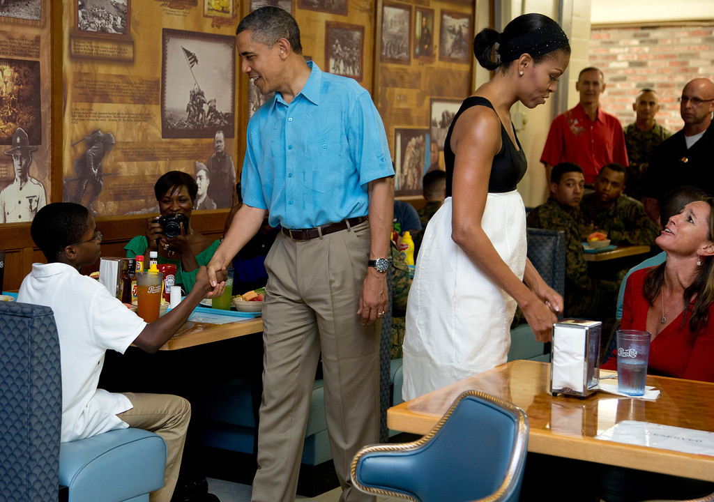 . President Barack Obama and first lady Michelle Obama visit with members of the military and their families in Anderson Hall at Marine Corp Base Hawaii, Tuesday, Dec. 25, 2012, in Kaneohe Bay, Hawaii. The first family was in Hawaii for a family holiday vacation. (AP Photo/Carolyn Kaster)