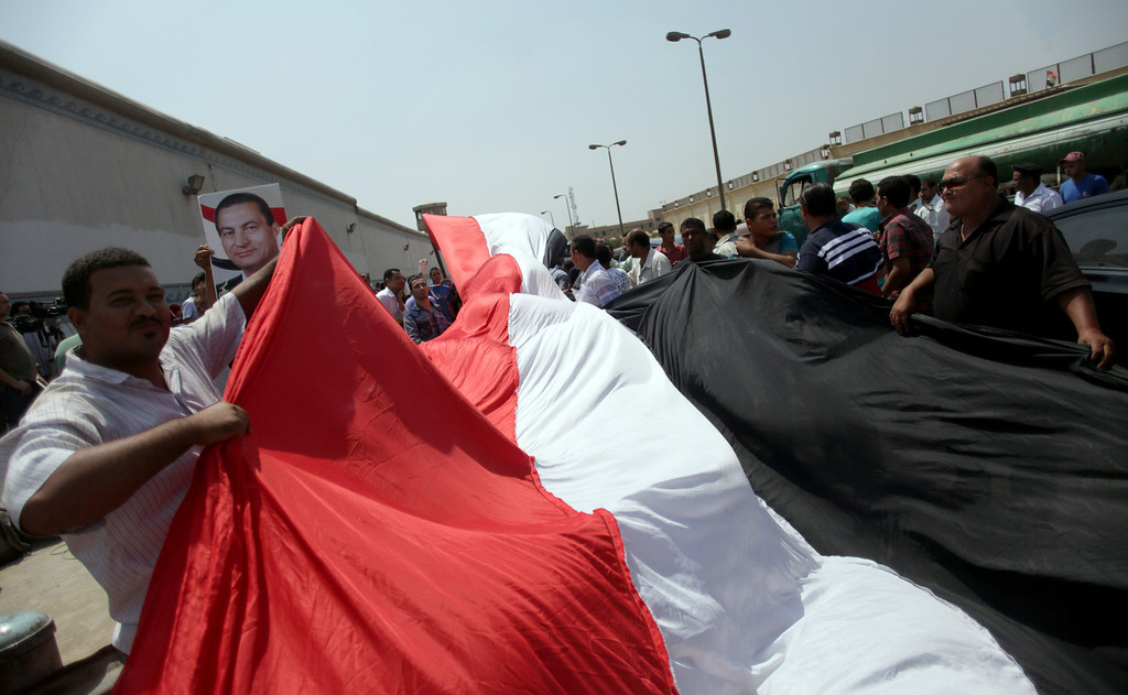. Supporters of Egypt\'s deposed autocrat Hosni Mubarak, wave a large national flag in front of Torah Prison where he is held, in Cairo, Egypt, Thursday, Aug. 22, 2013. A medically equipped helicopter landed Thursday at an Egypt prison Thursday to transport Hosni Mubarak from prison to his new home under house arrest, state TV reported, as dozens of the ousted leaderís supporters rallied outside waiting for the ousted leader to be released after more than two years in detention. (AP Photo/Khalil Hamra)