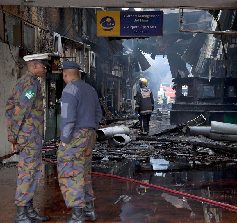 . Kenya Airforce personnel view the damage after fire engulf the international arrivals area of Jomo Kenyatta International Airport, Nairobi, Kenya, Wednesday, Aug. 7, 2013.  (AP Photo/Sayyid Azim)