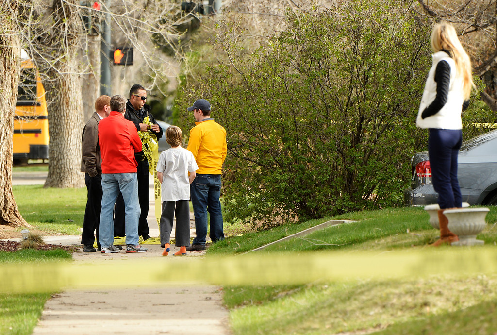 . Neighbors talk to police as they take down police tape while they investigate a homicide at a home in the 2100 block of South Saint Paul Street in Denver, Tuesday, April 15, 2014. A woman was found dead in a home near the University of Denver Monday night. (Photo by RJ Sangosti/The Denver Post)