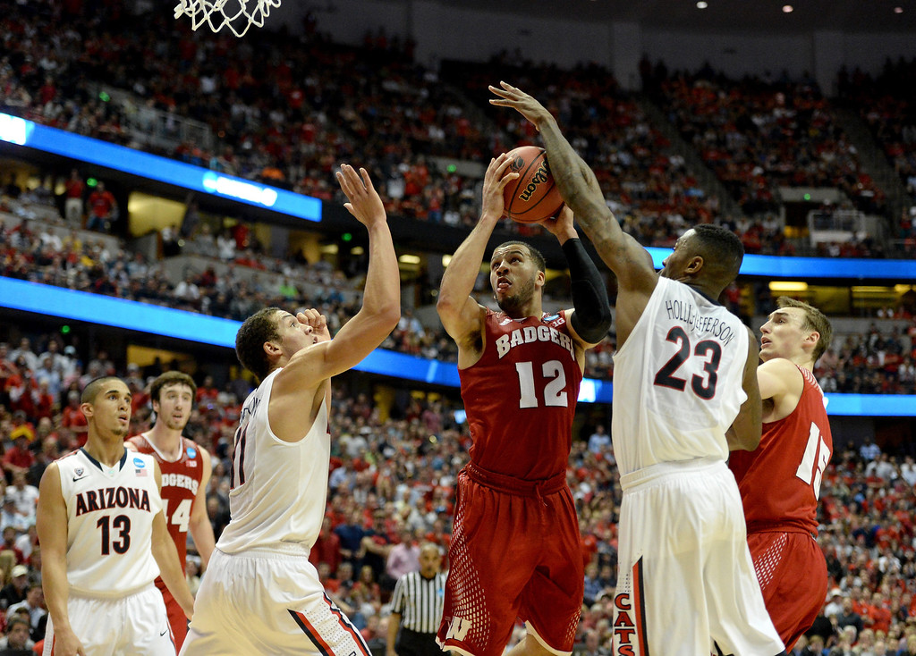 . Traevon Jackson #12 of the Wisconsin Badgers goes up for a shot between Aaron Gordon #11 and Rondae Hollis-Jefferson #23 of the Arizona Wildcats in the second half during the West Regional Final of the 2014 NCAA Men\'s Basketball Tournament at the Honda Center on March 29, 2014 in Anaheim, California.  (Photo by Harry How/Getty Images)