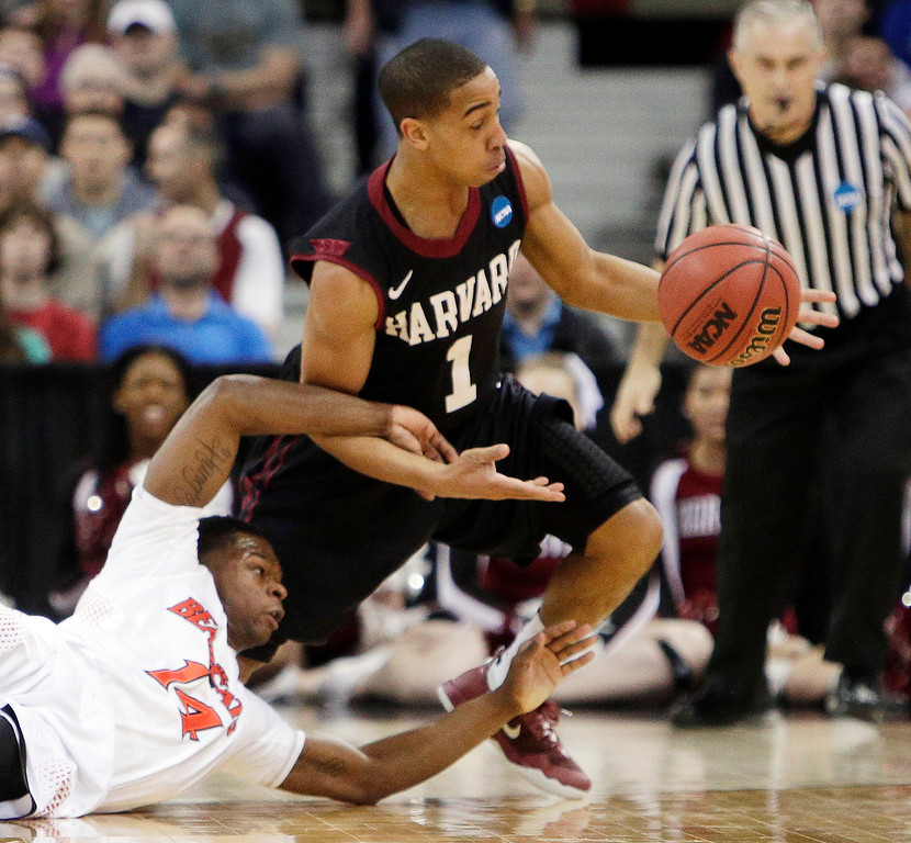 . Harvard\'s Siyani Chambers (1) and Cincinnati\'s Ge\'Lawn Guyn (14) fight for a loose ball in the second half during the second-round of the NCAA college basketball tournament in Spokane, Wash., Thursday, March 20, 2014. (AP Photo/Young Kwak)