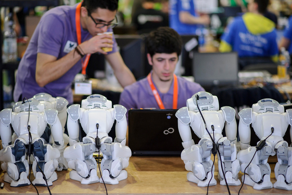 . Participants check robots at the 2014 RoboCup German Open tournament on April 03, 2014 in Magdeburg, Germany. The robots, which are models called Nao, manufactured by Aldebaran Robotics, perform autonomously and communicate with one another via WLAN. 950 participants from 12 countries are participating in the the three-day tournament that compete in a variety of disciplines, including soccer, rescue and dance. (Photo by Jens Schlueter/Getty Images)