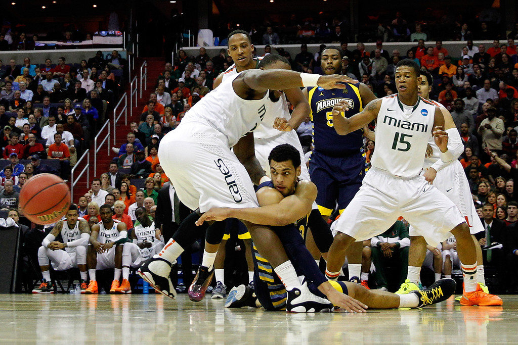 . WASHINGTON, DC - MARCH 28:  Trent Lockett #22 of the Marquette Golden Eagles passes the ball from the ground against Erik Swoope #21, Kenny Kadji #35 and Rion Brown #15 of the Miami (Fl) Hurricanes during the East Regional Round of the 2013 NCAA Men\'s Basketball Tournament at Verizon Center on March 28, 2013 in Washington, DC.  (Photo by Rob Carr/Getty Images)