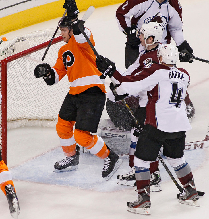 . Philadelphia Flyers\' Michael Raffl, left, raises his stick to celebrate his goal during the third period of an NHL hockey game in front of Colorado Avalanche players Matt Duchene, center, and Tyson Barrie, right, Thursday, Feb. 6, 2014, in Philadelphia. The Flyers won 3-1. (AP Photo/Tom Mihalek)