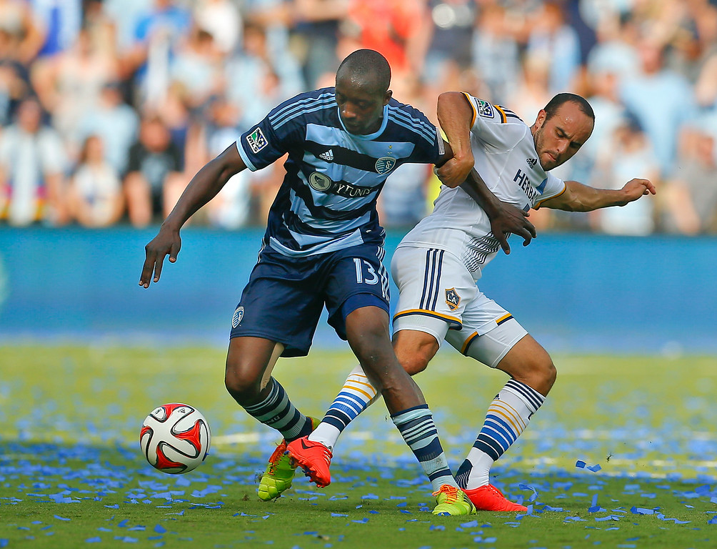 . Los Angeles Galaxy\'s Landon Donovan, right, battles for the ball against Sporting Kansas City\'s Lawrence Olum during the first half of an MLS soccer game Saturday, July 19, 2014, in Kansas City, Kan. (AP Photo/Topeka Capital-Journal, CHris Neal)