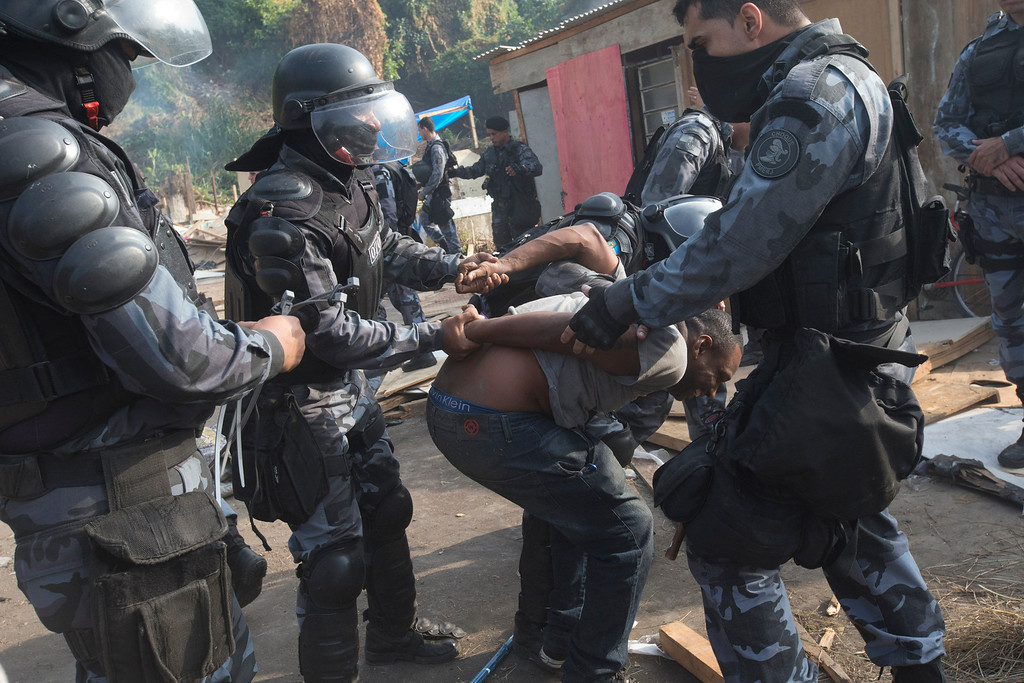 . Policemen detain a squatter during an eviction in Rio de Janeiro, Brazil, Friday, April 10, 2014. Squatters in Rio de Janeiro are clashing with police after a Brazilian court ordered that 5,000 people be evicted from abandoned buildings of a telecommunications company. Officers have used tear gas and stun grenades to try to disperse the families. (AP Photo/Silvia Izquierdo)