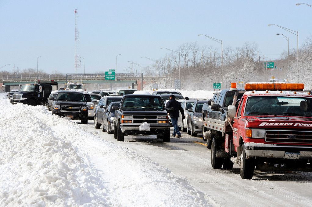 . Traffic is backed up on the Long Island Expressway just west of Exit 59 Ocean Avenue as payloaders clear snow from the road after a storm, Saturday, Feb. 9, 2013, in Ronkonkoma , N.Y. (AP Photo/Kathy Kmonicek)