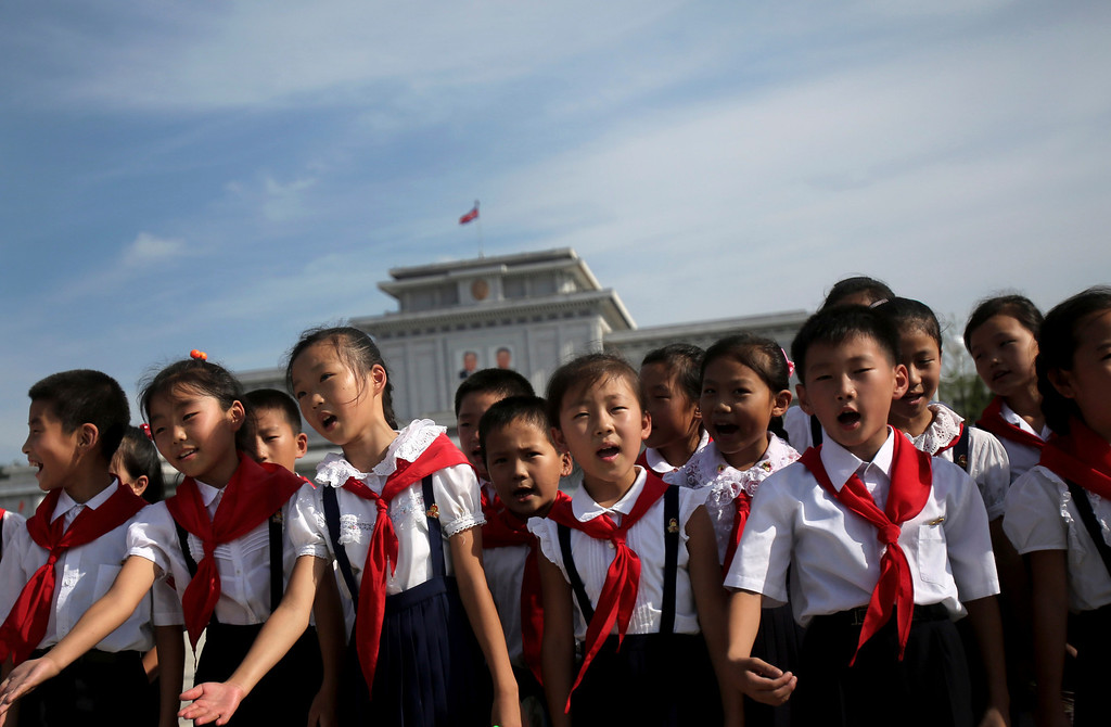 . North Korean schoolchildren sing in the park surrounding Kumsusan Palce of the Sun, the mausoleum where bodies of the late leaders Kim Il Sung and Kim Jong Il lie embalmed on Thursday, July 25, 2013 in Pyongyang, North Korea. (AP Photo/Wong Maye-E)