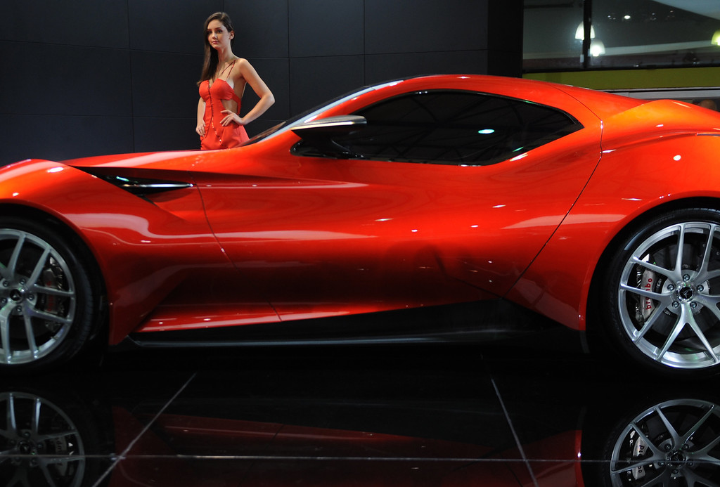 . This photo taken on April 20, 2013 shows a model posing next to an Icona design concept car on media day at the Shanghai auto show. The Shanghai auto show, which opens to the public on April 21, is expected to attract more than 800,000 visitors over the course of nine days.   PETER PARKS/AFP/Getty Images