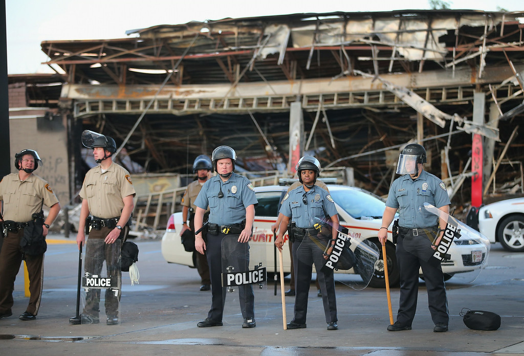 . Police guard a Quick Trip gas station that was burned yesterday when protests over the killing of 18-year-old Michael Brown turned to riots and looting on August 11, 2014 in Ferguson, Missouri. Police responded with tear gas and rubber bullets as residents and their supporters protested the shooting by police of an unarmed black teenager named Michael Brown who was killed Saturday in this suburban St. Louis community. Yesterday 32 arrests were made after protests turned into rioting and looting in Ferguson.  (Photo by Scott Olson/Getty Images)