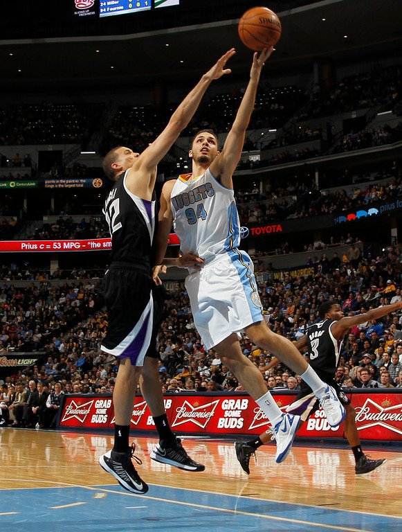 . Denver Nuggets guard Evan Fournier, right, goes up for a shot past Sacramento Kings guard Francisco Garcia during the fourth quarter of the Nuggets\' 121-93 victory in an NBA basketball game in Denver on Saturday, Jan. 26, 2013. (AP Photo/David Zalubowski)