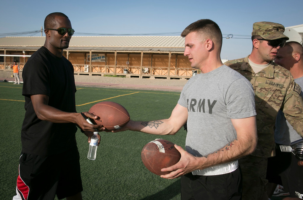. Denver Broncos cornerback Champ Bailey gives an autographed football to a soldier following an impromptu touch football game with service members stationed in the Middle East during a stop of his week-long USO/NFL tour March 16, 2013.  Bailey, along with five other NFL players, are in the region visiting multiple military sites, spending time with troops and sharing football techniques. USO Photo by Fred Greaves