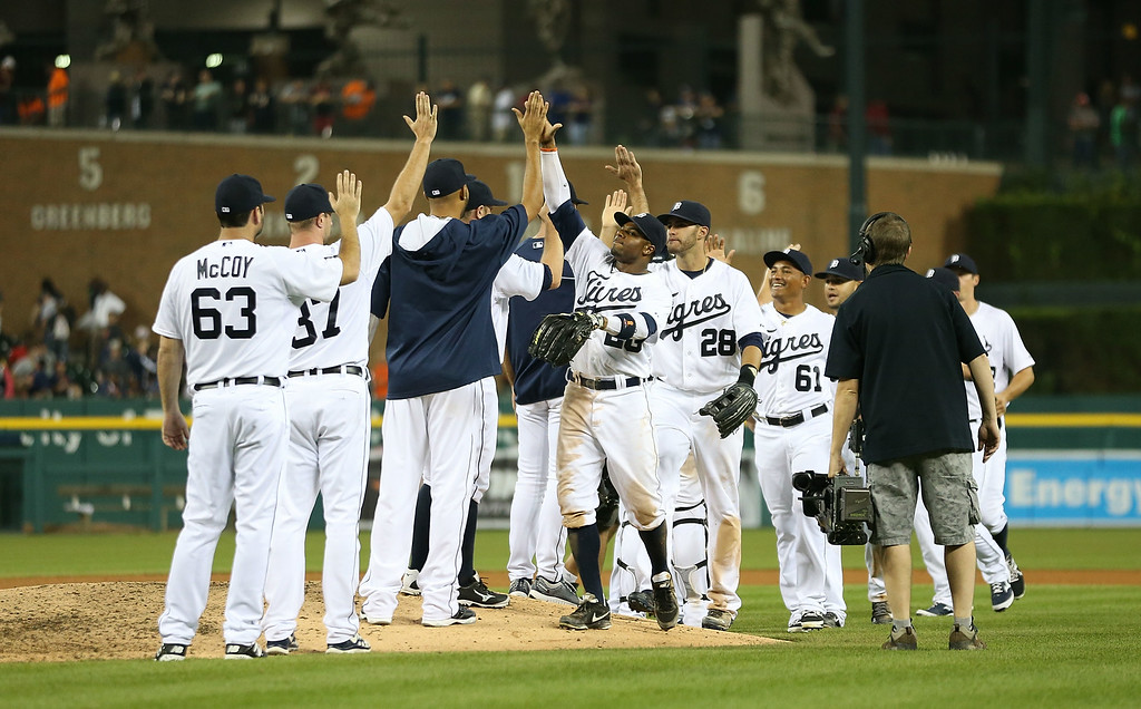 . DETROIT, MI - AUGUST 02: Rajai Davis #20 of the Detroit Tigers celebrates with his teammates after defeating the Colorado Rockies at Comerica Park on August 2, 2014 in Detroit, Michigan. The Tigers defeated the Rockies 11-5.  (Photo by Leon Halip/Getty Images)