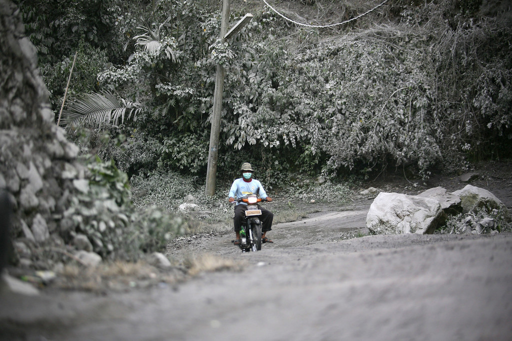 . A man wearing a mask rides on his motorbike through a road covered with volcanic ash from Mount Sinabung\'s eruption in Mardingding, North Sumatra, Indonesia, Monday, Nov. 4, 2013.  The volcano erupted Sunday, unleashing volcanic ash high into the sky and forcing the evacuation of villagers living around its slope. (AP Photo/Binsar Bakkara)