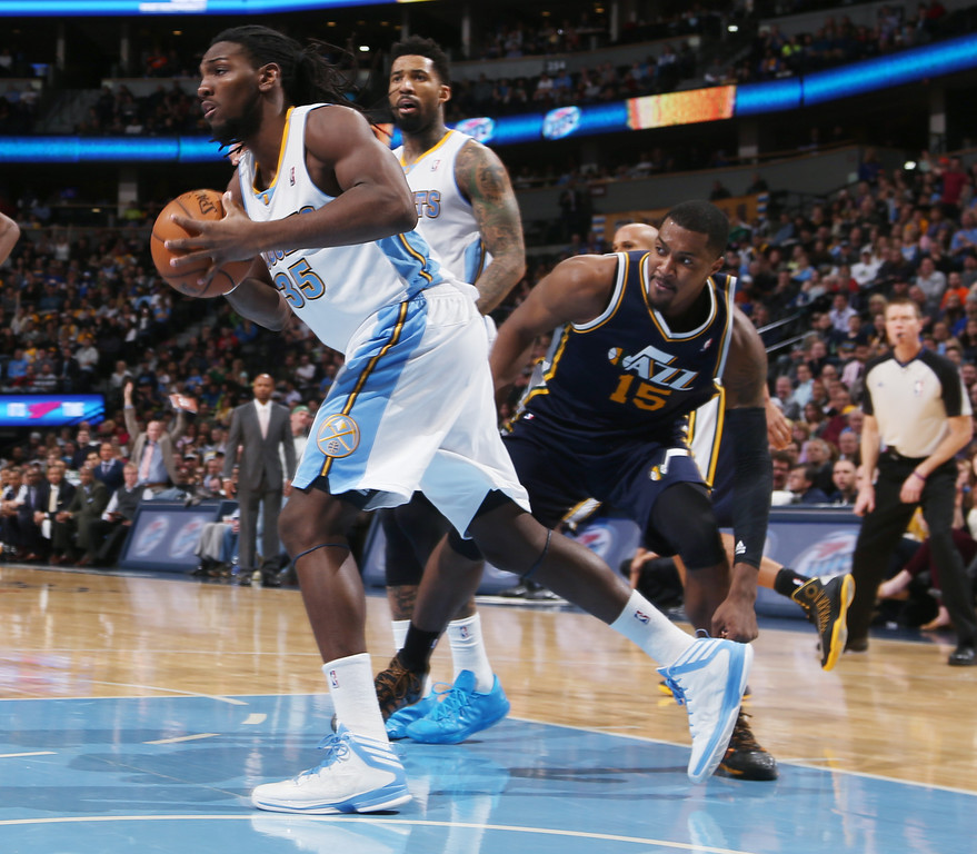 . Denver Nuggets forward Kenneth Faried, front, left, pulls in a loose ball as Utah Jazz center Derrick Favors, front right, and Nuggets forward Wilson Chandler, back, look on in the fourth quarter of Utah\'s 103-93 victory in an NBA basketball game in Denver on Friday, Dec. 13, 2013. (AP Photo/David Zalubowski)