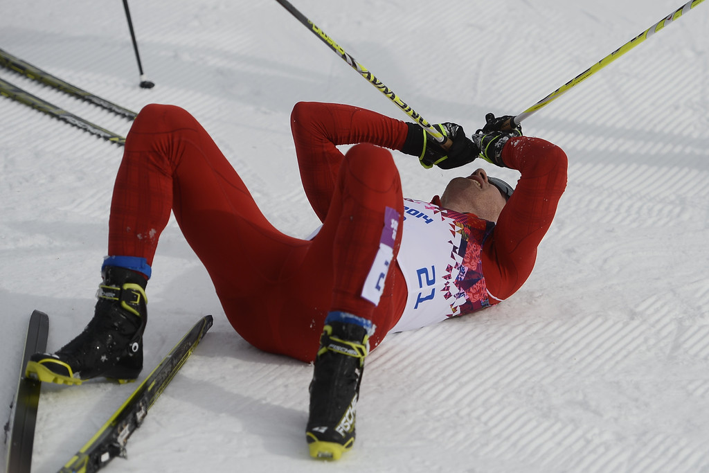 . Switzerland\'s Dario Cologna lies on the snow after winning the Men\'s Cross-Country Skiing 15km + 15km Skiathlon at the Laura Cross-Country Ski and Biathlon Center during the Sochi Winter Olympics on February 9, 2014, in Rosa Khutor.  PIERRE-PHILIPPE MARCOU/AFP/Getty Images
