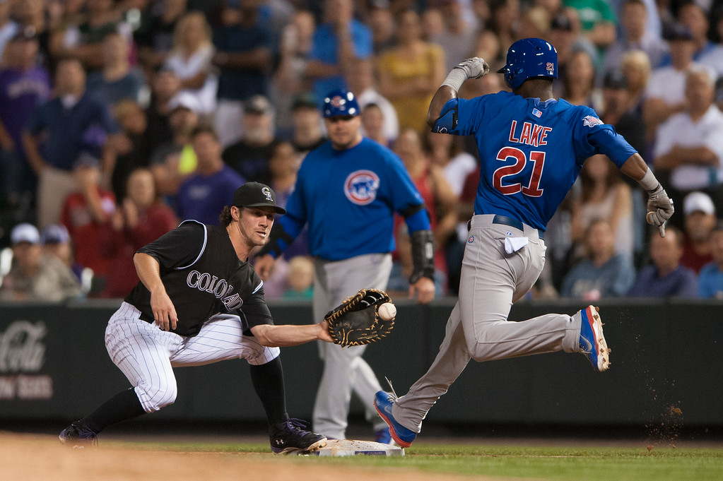 . DENVER, CO - AUGUST 06:  Charlie Culberson #23 of the Colorado Rockies has Junior Lake #21 of the Chicago Cubs out on a close play that was reviewed by the umpires and would prove to be the final out in the ninth inning of the game at Coors Field on August 6, 2014 in Denver, Colorado.  (Photo by Dustin Bradford/Getty Images)