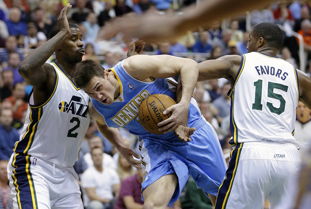 . Denver Nuggets\' Danilo Gallinari, center, drives to the basket as Utah Jazz\'s Marvin Williams (2) and teammate Derrick Favors (15) defend in the second quarter during an NBA basketball game on Wednesday, April 3, 2013, in Salt Lake City. (AP Photo/Rick Bowmer)