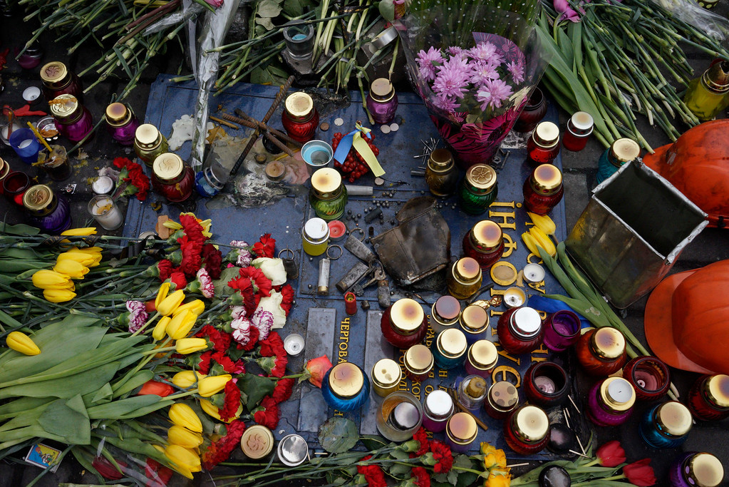 . Flowers and candles cover the spot where a protester was killed in a recent clash with riot police in Kiev\'s Independence Square, Ukraine, Friday, Feb. 28, 2014. Official reports say 82 people were killed in severe clashes between opposition activists and riot police.  (AP Photo/Efrem Lukatsky)